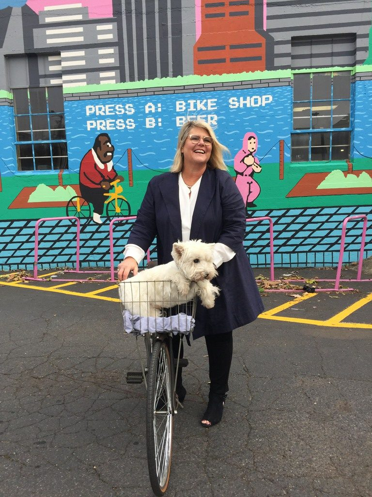 Susie Hunt Moran realtor with a bike and dog